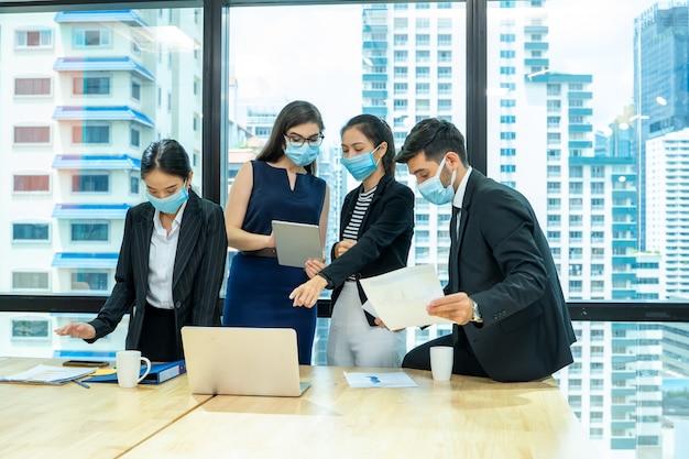 Funcionário do grupo usando máscara facial médica trabalhando de acordo com a política de distanciamento social no escritório comercial durante nova mudança normal após coronavírus ou situação de pandemia pós-surto de covid-19.