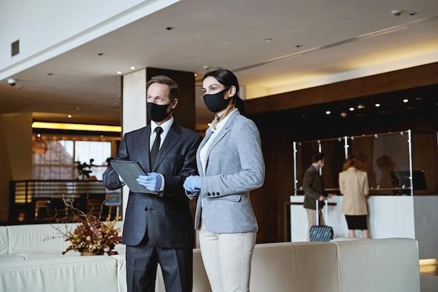 Funcionário do hotel trabalhando em equipe enquanto os hóspedes chegam