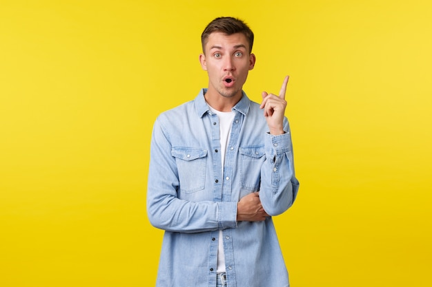 Funcionário do sexo masculino, criativo e animado, tem sugestões, expressa sua própria visão durante a reunião de escritório. cara bonito levanta o dedo indicador em gesto de eureka, dizendo sua ideia em voz alta, fundo amarelo.
