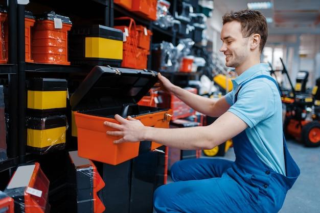 Funcionário do sexo masculino em uniforme escolhendo caixa de ferramentas na loja de ferramentas