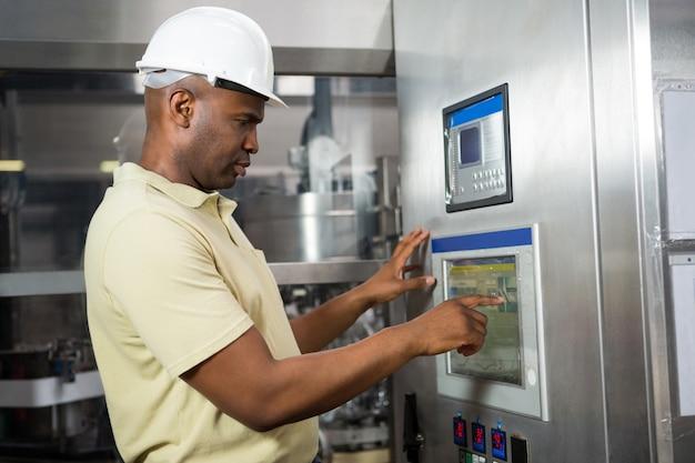 Funcionário do sexo masculino operando máquina na indústria de manufatura