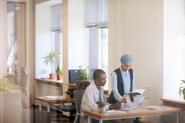 Funcionário do sexo masculino se acostumando com seu novo trabalho de escritório enquanto trabalha no laptop na mesa