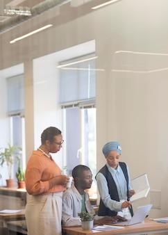 Funcionário do sexo masculino se acostumando com seu novo trabalho de escritório junto com colegas do sexo feminino