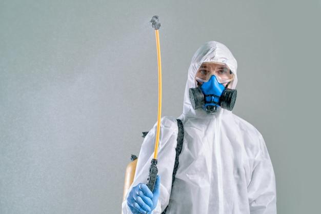 Funcionário dos serviços de descontaminação fazendo a descontaminação do quarto. foto com uma cópia-espaço.