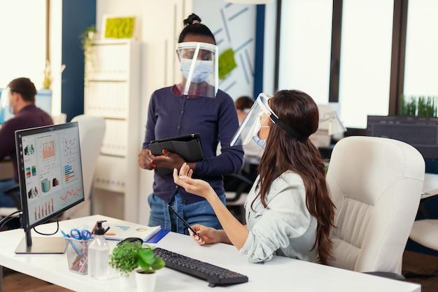 Funcionário e gerente africano discutindo estratégia usando máscara facial contra covid19. equipe diversificada trabalhando respeitando o distanciamento social durante a pandemia global de coronavírus. novo normal.