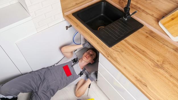 Funcionário habilidoso em uniforme cinza e luvas deita-se no chão e desparafusa detalhes consertando o coletor de lixo sob a pia na vista da cozinha de cima
