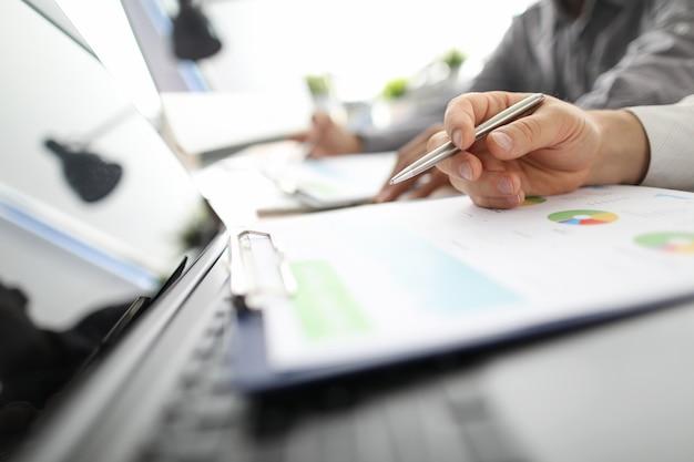 Funcionário masculino, fazendo anotações com caneta prata no relatório anual
