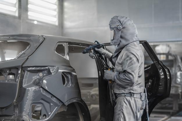 Funcionário pintando a carroceria do carro