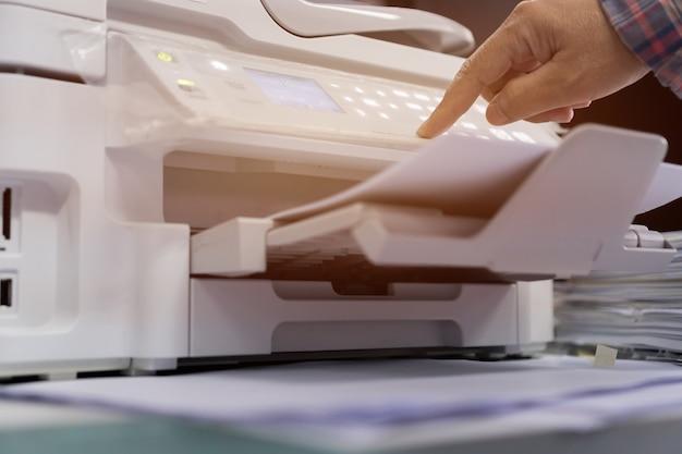Funcionário, pressionando o botão no painel da impressora