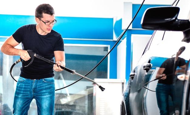 Funcionário profissional da lavagem de carros lavando carro na estação de lavagem