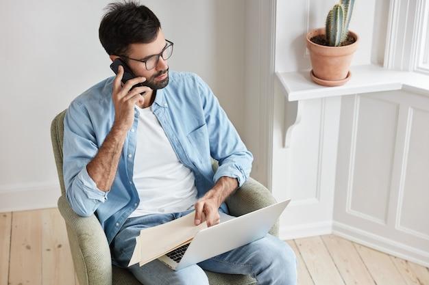 Funcionário próspero de sucesso dirige negócios, completa vendas com o parceiro via telefone celular, trabalha com laptop