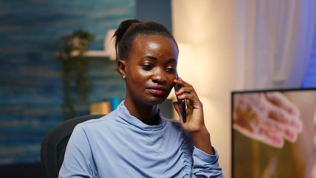 Funcionário remoto preto falando no telefone enquanto trabalhava no laptop à noite. freelancer com foco ocupado, usando rede de tecnologia moderna sem fio, fazendo horas extras para leitura de trabalho, pesquisando, fazendo uma pausa