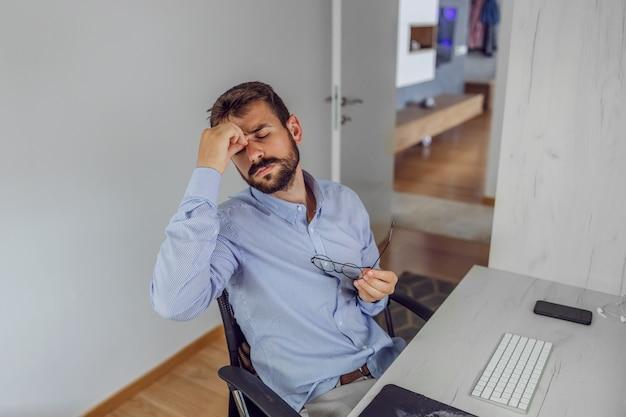 Funcionário sentado em seu escritório em casa e com dor de cabeça