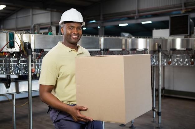 Funcionário sorridente carregando caixa de papelão em uma fábrica de suco