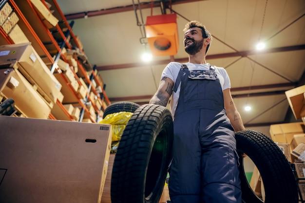 Funcionário sorridente que realoca pneus enquanto caminha no depósito de uma empresa de importação e exportação.