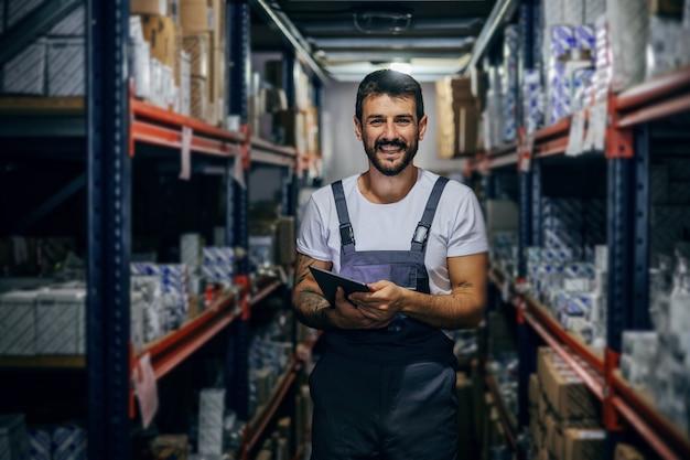 Funcionário trabalhador tatuado barbudo sorridente segurando o tablet e parado no armazenamento.