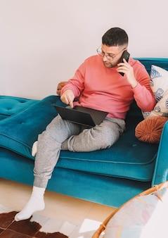 Funcionário trabalhando no sofá de casa com seu laptop devido à pandemia de coronavírus