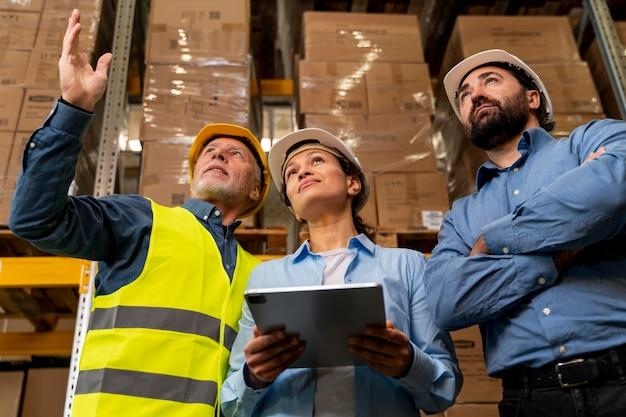Funcionários com capacete trabalhando em depósito