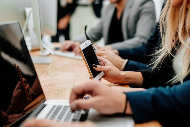 Funcionários com dispositivos inteligentes sentados na mesa