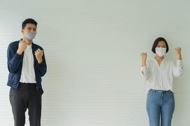 Funcionários com máscara facial de pé e mão levantada juntos para alegre