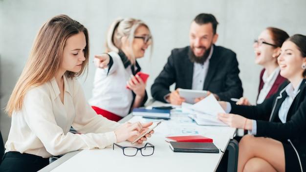 Funcionários corporativos. intimidação e zombaria. reunião da equipe de negócios. mulher apontar o dedo para um colega chateado, verificando o smartphone.