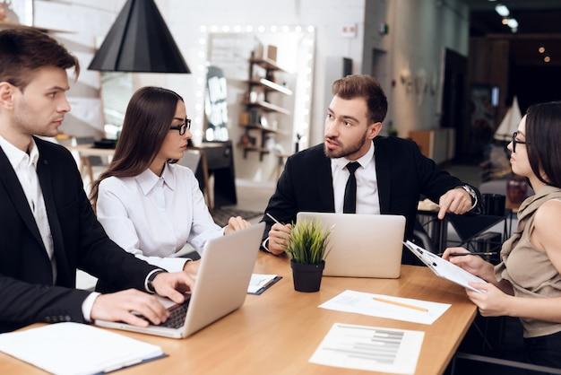 Funcionários da empresa realizam uma reunião na mesa.