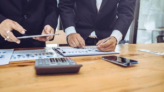 Funcionários da empresa usando o tablet com gráfico de negócios.