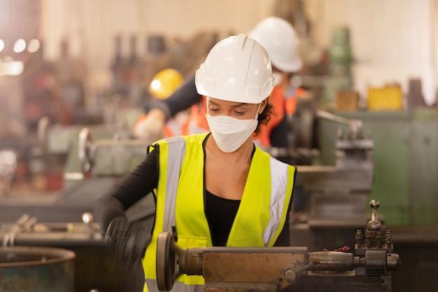 Funcionários da fábrica pessoas usando máscara facial e roupa de segurança. mulheres que trabalham na fábrica.