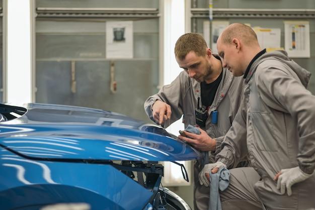 Funcionários da oficina de pintura de carrocerias verificam a qualidade