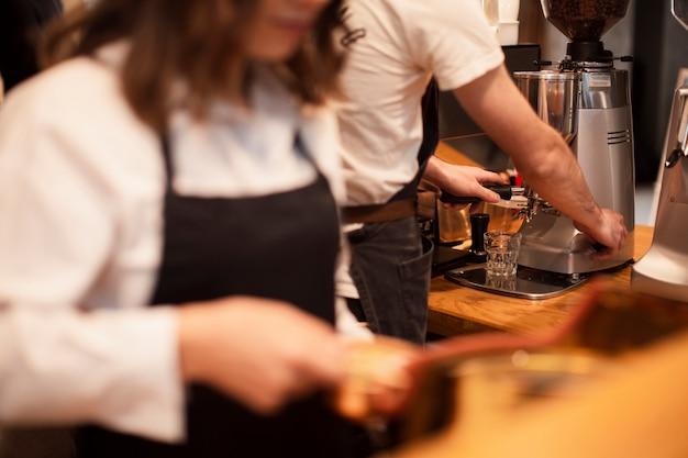 Funcionários de cafeteria trabalhando em máquinas de café