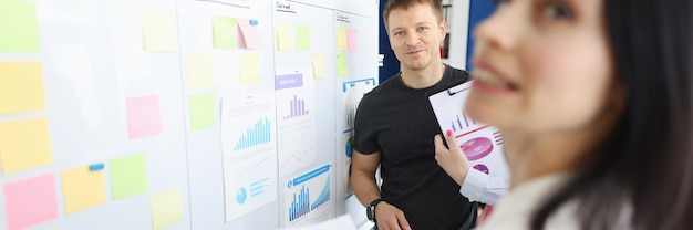 Funcionários de escritório discutindo números de negócios no quadro branco