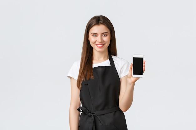 Funcionários de mercearia, conceito de pequenas empresas e cafés. barista alegre e bonito de avental preto mostrando a tela do smartphone. recomenda o download do aplicativo de compras online
