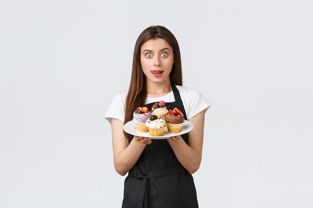 Funcionários de mercearia, conceito de pequenas empresas e cafés. bonito jovem barista feminino no avental preto segurando saborosa sobremesa, desejo de lamber os lábios ter uma mordida de deliciosos bolinhos, fundo branco.