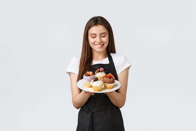 Funcionários de mercearia, conceito de pequenas empresas e cafés. garçonete boba alegre quer comer um pedaço de cupcakes deliciosos. barista mordendo o lábio tentador provar novas sobremesas, fundo branco.