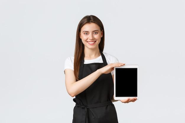 Funcionários de mercearia, conceito de pequenas empresas e cafés. sorridente vendedora da loja fofa no avental preto, mostrando a tela do tablet digital. trabalhador do café sugere pedido online