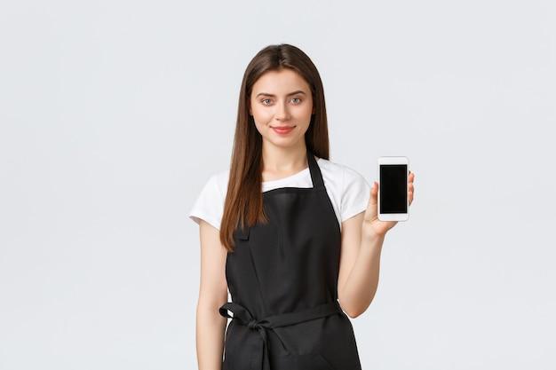 Funcionários de mercearia, conceito de pequenas empresas e cafés. vendedora sorridente fofa recomenda baixar o aplicativo de compras online, mostrando a tela do smartphone, aplicativo de publicidade.