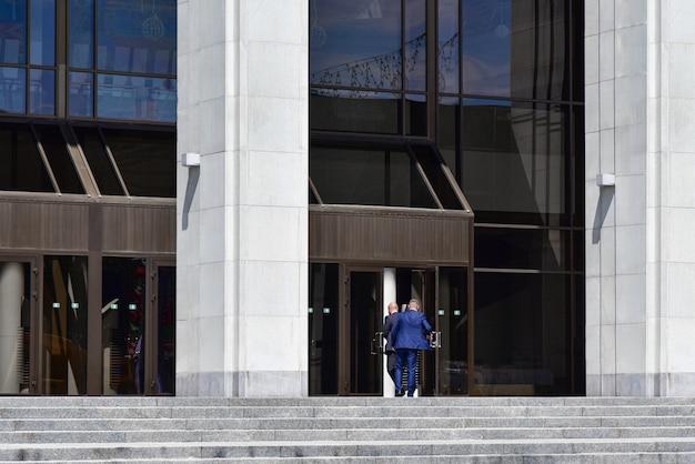 Funcionários de terno entram na porta de um grande prédio administrativo