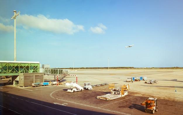 Funcionários do aeroporto recebendo transporte de bagagem na pista de pouso e um avião decolando em segundo plano