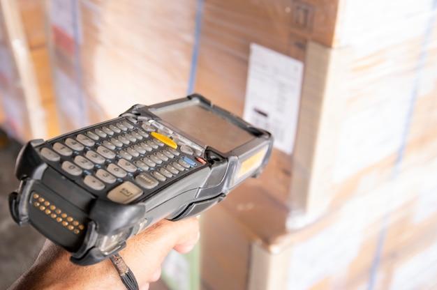 Funcionários do armazém estão segurando o scanner de código de barras com digitalização no rótulo da remessa.