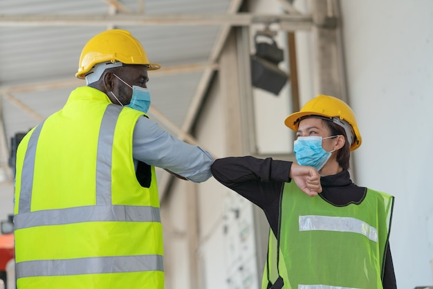 Funcionários do armazém usando máscara facial para proteger o coronavírus, cumprimentando cotovelos na fábrica do armazém de logística