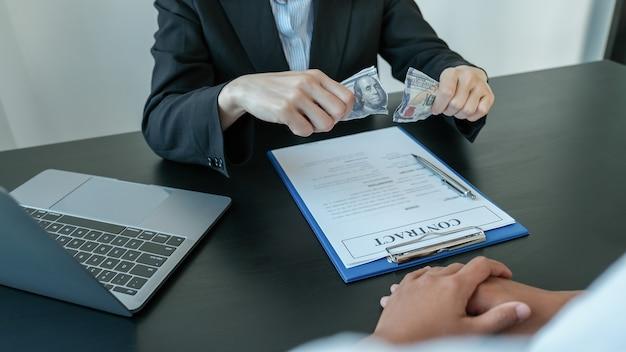 Funcionários do governo rasgam a nota de um dólar recusando-se a aceitar o dinheiro do suborno da empresária, o conceito de corrupção e anti-suborno.