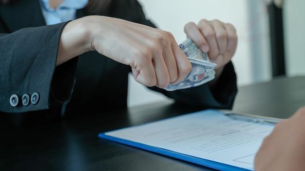 Funcionários do governo rasgam a nota de um dólar recusando-se a aceitar o dinheiro do suborno.