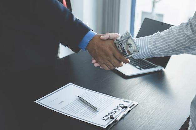 Funcionários do governo recebendo dinheiro de suborno de empresário ao apertar as mãos conceito de corrupção