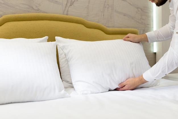 Funcionários do hotel configurar travesseiro na cama