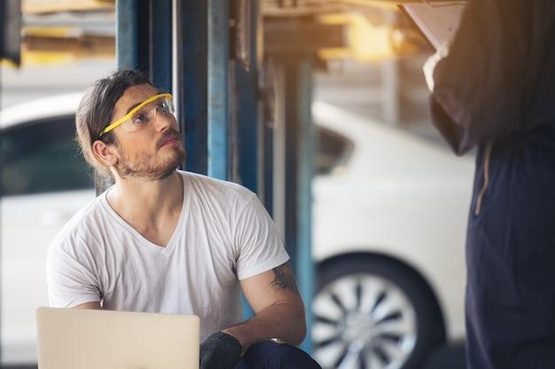 Funcionários do serviço de automóveis inspecionam a parte inferior e as placas de proteção sob o carro levantado
