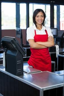 Funcionários do sexo feminino em pé no balcão de caixa