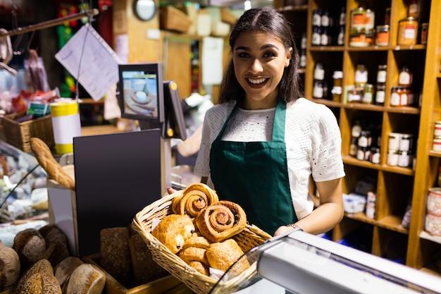 Funcionários do sexo feminino segurando croissant na cesta de vime no balcão de pão