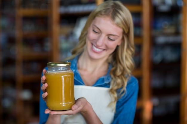 Funcionários do sexo feminino segurando o pote de mel no supermercado
