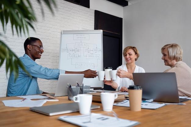 Funcionários em reuniões de negócios tilintando xícaras