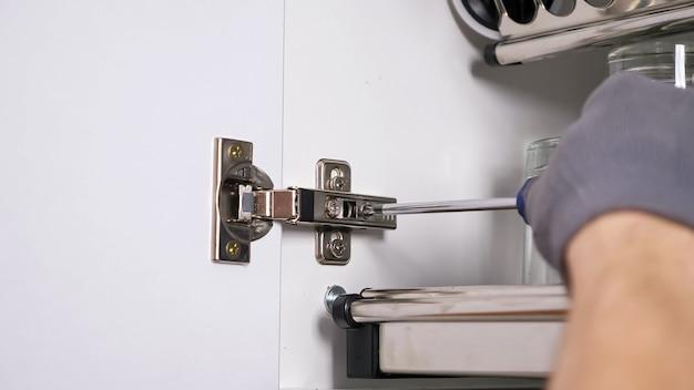 Funcionários habilidosos com luvas de tecido cinza instalam a porta do gabinete branco, torcendo os parafusos nas dobradiças da cozinha vista de perto